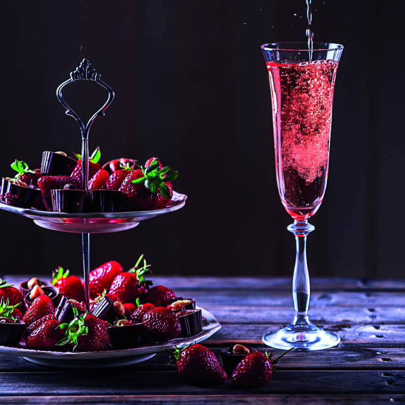 Sparkling pink wine is poured in glass. Stand with strawberries and sweets on a wooden table.