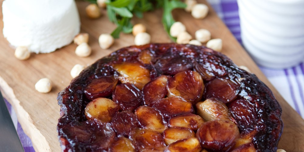 Tatin of shallots and port with creamy goat's cheese served on a wooden board