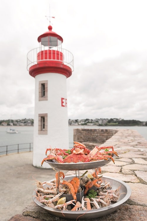 Lighthouse with seafood in front of it