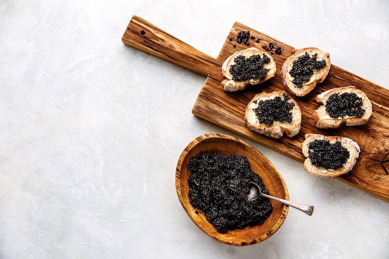 Caviar on bread set on a wooden board