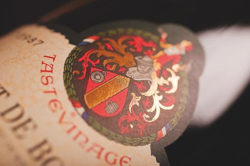 a Confrerie des Chevaliers du Tastevin crest on a bottle of Cremant de Bourgogne wine bottle label closeup