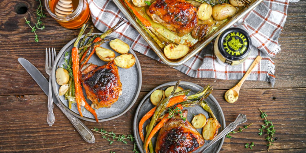 An image of a sheet pan and plates full of chicken and vegetables with Maille Rich Country