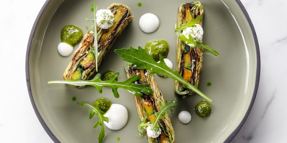 Layered arugula pistou, pointed cabbage, and grilled avocado